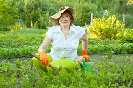 prong: Happy mature woman working in her vegetable garden