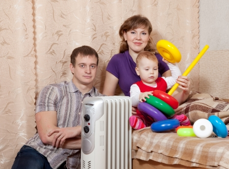 calorifer: parents and child relaxing near warm radiator  in home