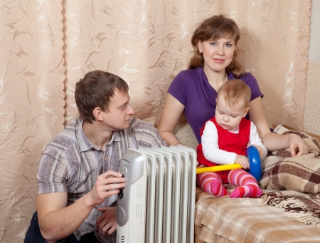 parents and child relaxing near warm radiator  in home