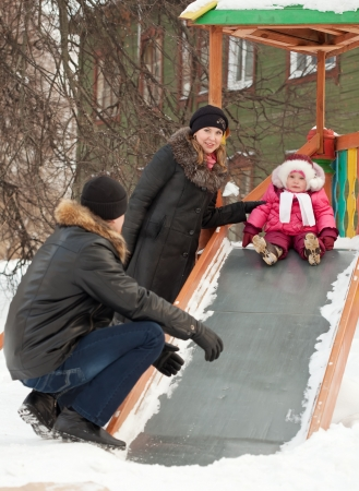 happy parents with  toddler playing on slide in winter photo
