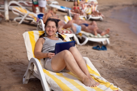 Happy mature woman  with laptop at resort beach photo