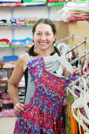 Mature woman  chooses dress at fashionable shop photo