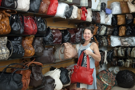 Mature woman chooses leather bag at  shop photo