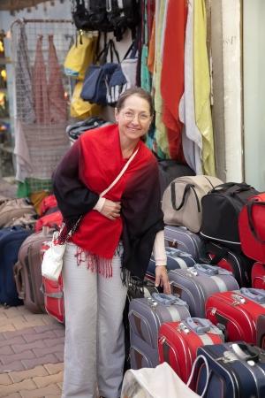 Mature woman chooses suitcase at  shop Stock Photo - 15183457