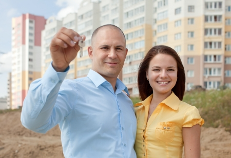 homeownership: happy young family with key  in front of new home