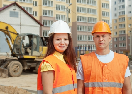 Portrait of two builders works at construction site  photo