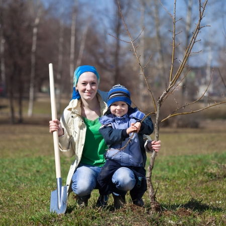 young woman with her son planting the tree outdoor photo