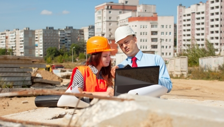 Two architects wearing protective helmet standing in front of building site photo