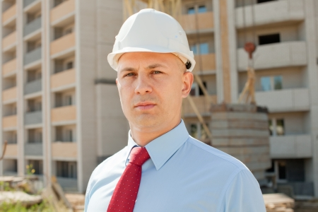 White-collar worker wearing protective helmet works on the building site photo