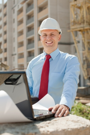 construction manager: Happy builder in hardhat works on the building site Stock Photo