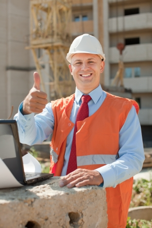Happy builder in hardhat works on the building site photo