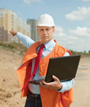 Portrait of builder works at construction site  photo