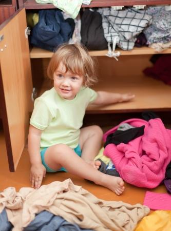 Baby girl  chooses dress in parents wardrobe  Stock Photo