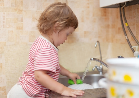 Baby girl  washes dishes in kitchen photo