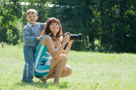 Happy mother with boy taking photo on grass in park photo