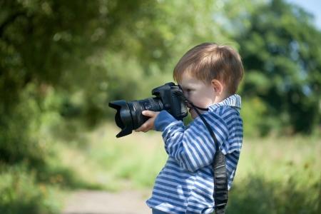 Kleine jongen met digitale camera maakt foto outdoor Stockfoto