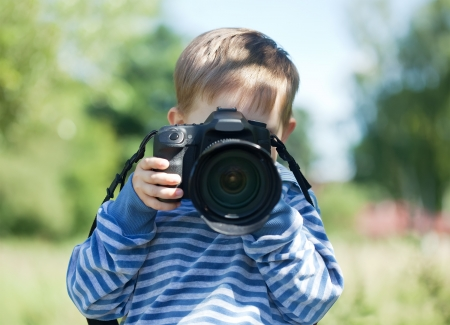 takes:  Young photographer with  digital camera takes photo outdoor Stock Photo