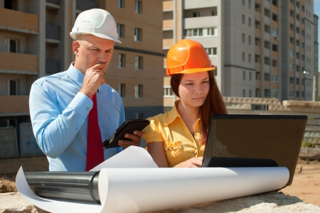 Two architects wearing protective helmet works in front of building site Stock Photo - 14968366