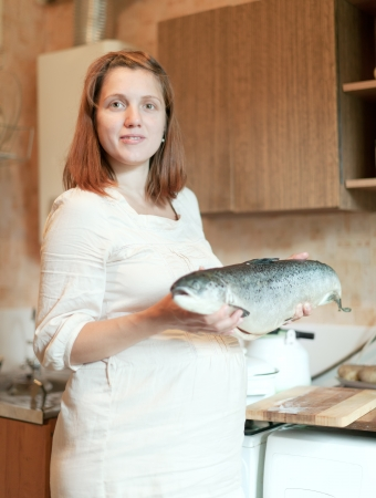 pregnant woman with salmon in the kitchen  photo