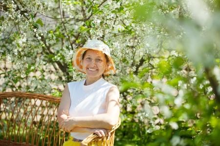 Happy mature woman relaxing in bloom garden Stock Photo - 15044873