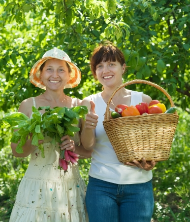 Two happy women with  harvested vegetables in garden photo
