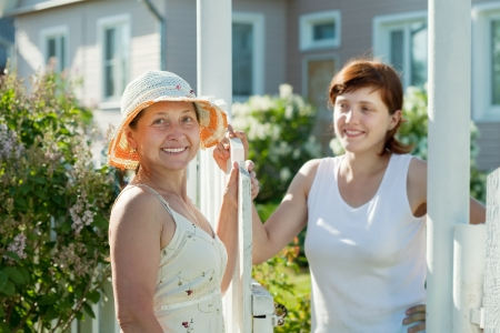 wicket door: Two happy women near fence wicket. Selective focus on left woman Stock Photo