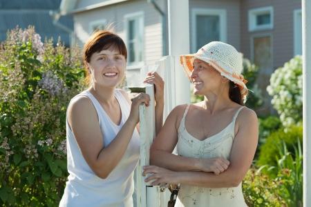 wicket gate: Two happy women near fence wicket  in front of home
