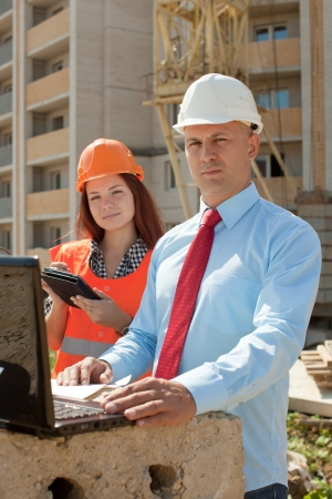 two builders wearing protective helmet works on the building site photo