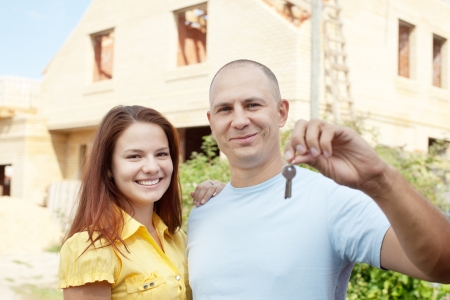 Happy couple with key against building new brick house Stock Photo - 15044898
