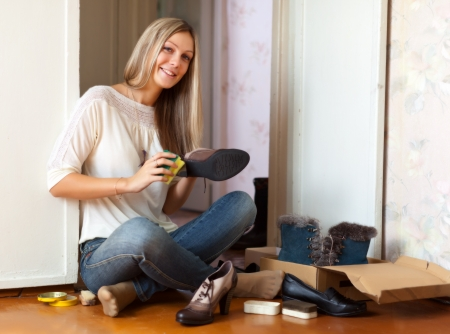 footware: Woman sits on floor and cleans shoes Stock Photo