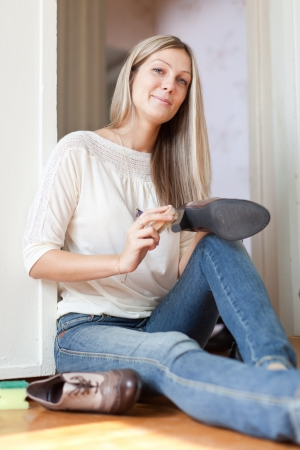 Woman sits on floor and cleans footwear photo