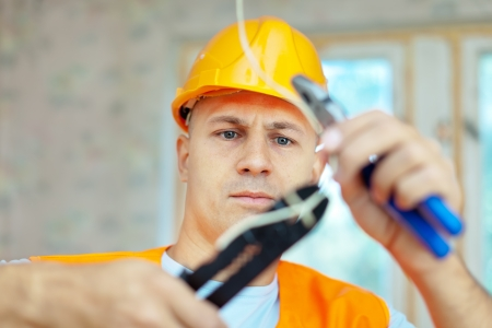 electrical wires: electrician installing electricity in a new house Stock Photo