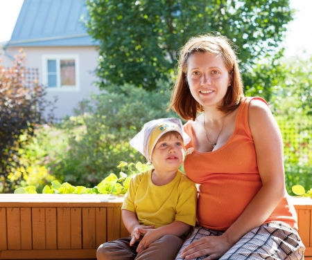 gravida: Happy mother and child sits on bench in veranda