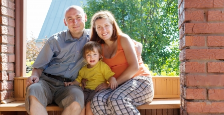 Happy family of three sits on bench in summer veranda  photo