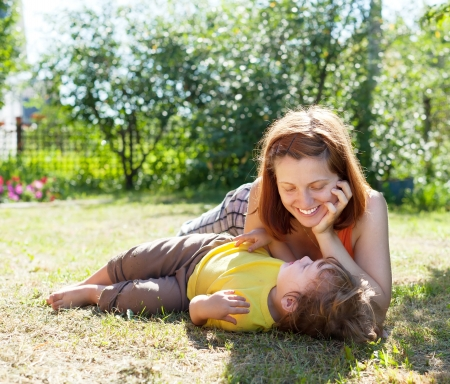 gravida: Happy mother and child laying on grass in yard