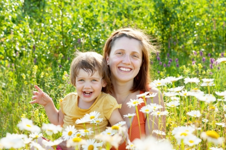 Happy mother with child sits in camomile plant Stock Photo - 15087405