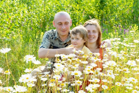 Happy parents with child sits  in summer daisy plant photo