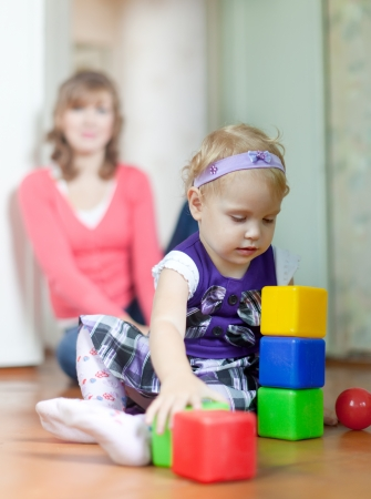 baby girl plays with blocks in home interior photo