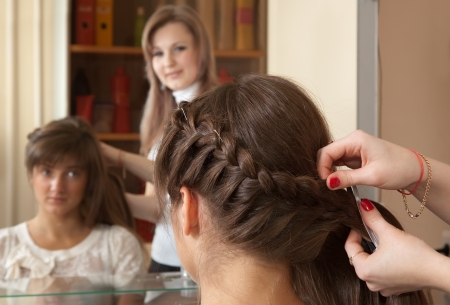hair stylist works on woman hair in salon photo