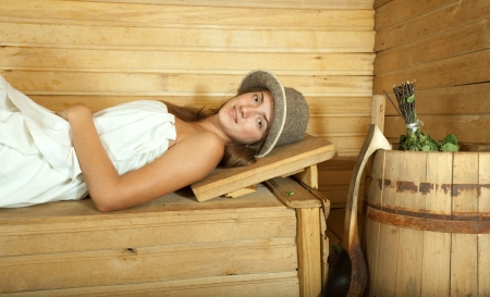 stive: Young woman lying on wooden bench in sauna
