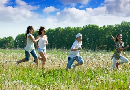 Four friends running at meadow in summer photo
