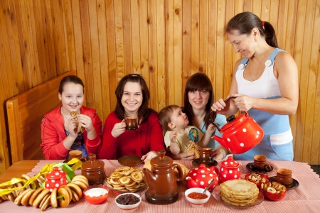 banket: Women drinks tea with pancakes during  Pancake Week in Russia Stock Photo