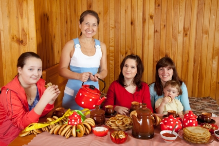 Happy family  drinking tea with russian traditional snack photo