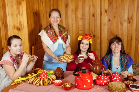 Women  drinks tea and eats pancakes  in home photo