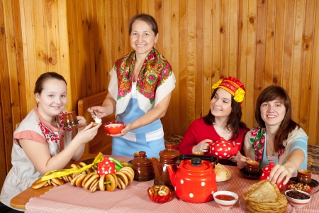 banket: Women in traditional clothes drinks tea and eats pancake   Stock Photo