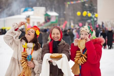 maslenitsa: People in traditional  clothes eating pancake during  Maslenitsa festival
