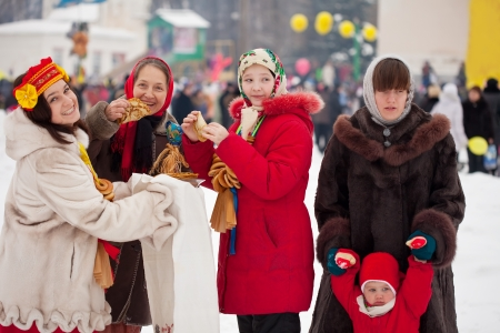 Women eating pancakes during  Shrovetide in Russia photo