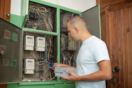 electrician working with electric box at house photo