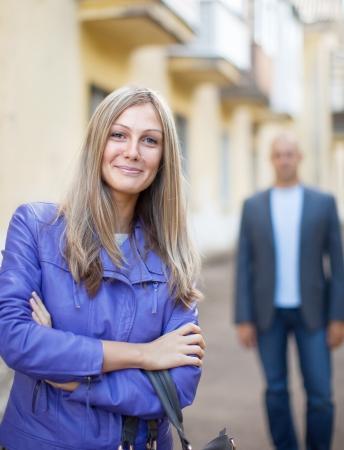 Man walks behind woman on the city street Stock Photo