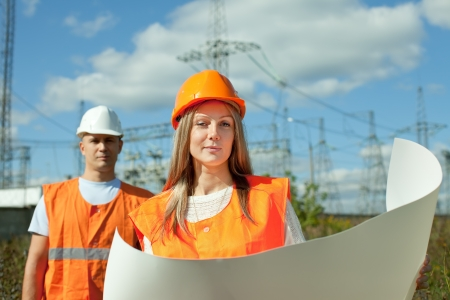 two workers wearing protective helmet works at electrical power station photo